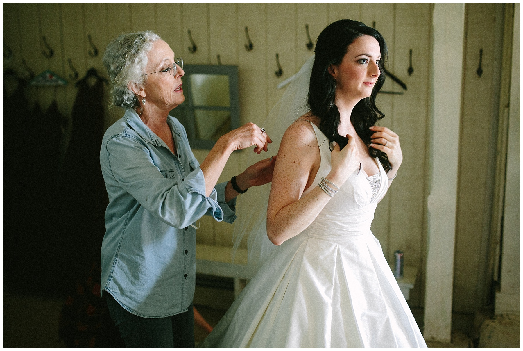 mom helping bride dress